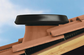 Roof mounted ventilation fan with a flashing that integrates with a tiled roof structure.